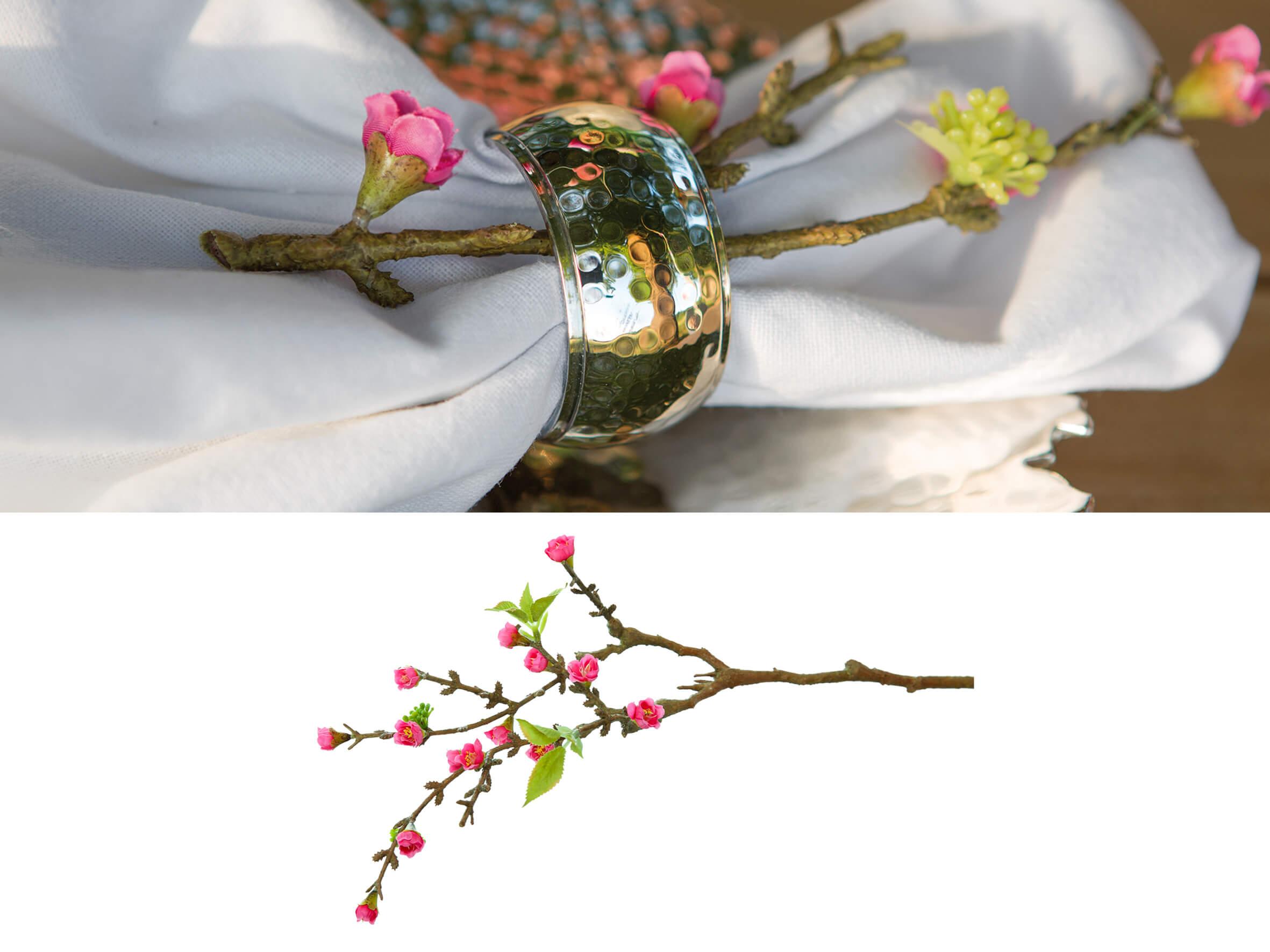 Dekoratives Platzgedeck aus Stoffserviette, Serviettenring und Blütenzweig.
